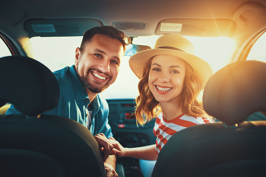 Contact - Happy Young Couple Sitting In Car Going On A Road Trip Together